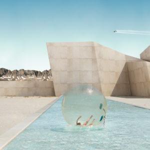 mensch als weltkugel dreht im wasser vor architektur